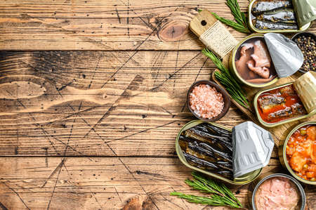 Various canned fish and seafood in a metal cans. Wooden background. Top view. Copy space