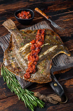 Grilled Flounder or plaice with tomato sauce on wooden cutting board. Dark wooden background. Top view
