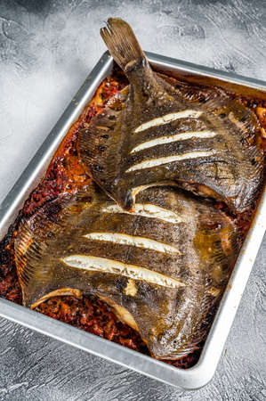 Flounder flat fish roasted in a tomato sauce in baking tray. White background. Top view