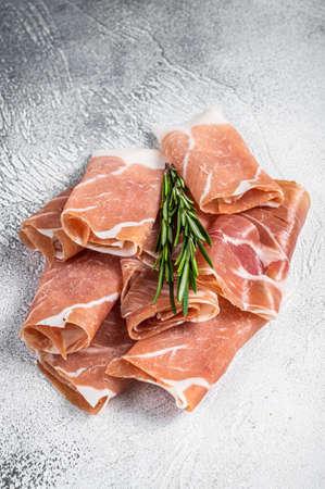 Italian prosciutto crudo parma ham on a table. White background. Top View