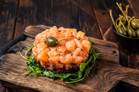 Salmon tartare or tartar with red onion, avocado, arugula and capers. Dark wooden background. Top View Foto de archivo