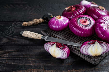 Whole and halfed Flat red sweet onion on a cutting board. Black Wooden background. Top View. Copy space