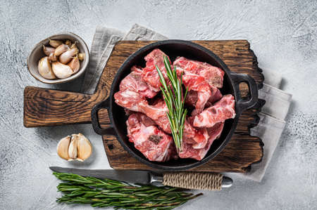 Raw diced meat cubes with bone in a pan. White background. Top View Foto de archivo