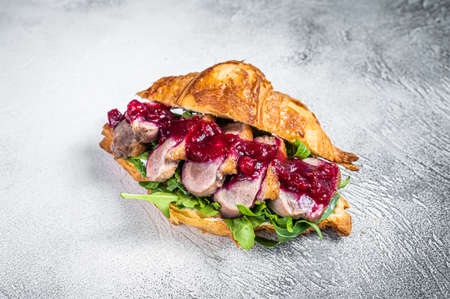 Duck breast Croissant sandwich with steak slices, arugula and sauce. White background. Top View Foto de archivo