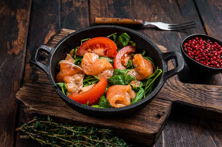 Fresh salmon salad with arugula, tomato and green vegetables. Dark wooden background. Top View Foto de archivo