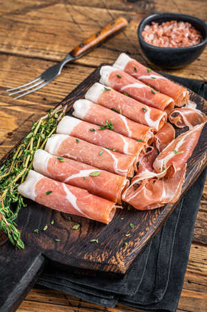 Prosciutto crudo Dry cured parma ham on a wooden cutting board with thyme. wooden background. Top View