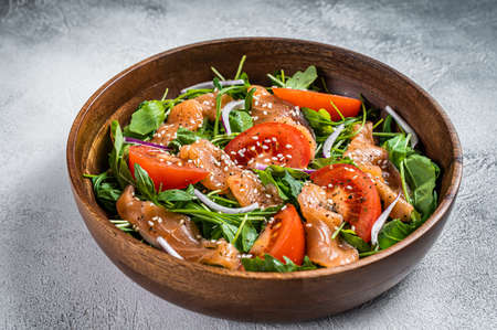 Smoked salmon salad with arugula, tomato and green vegetables. White background. Top View
