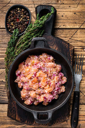 Tartar or tartare with salmon fish, red onion, arugula and capers in a pan. Wooden background. Top View Foto de archivo
