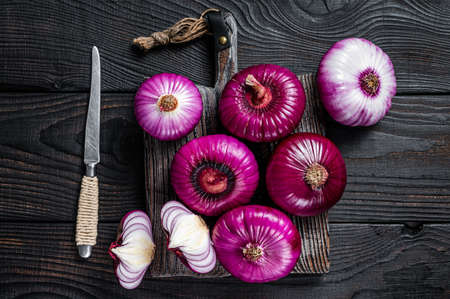 Whole and halfed Flat red sweet onion on a cutting board. Black Wooden background. Top View