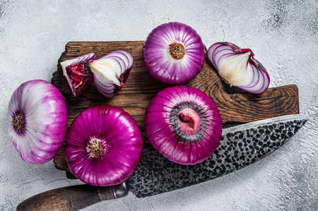 Sliced Flat red sweet onion on a cutting board. White background. Top View