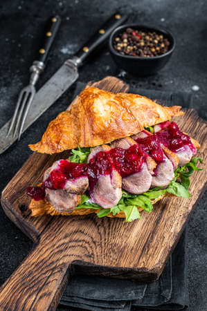Croissant sandwich with Duck breast steak slices, arugula and sauce. Black background. Top View Foto de archivo