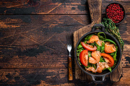 Fresh salmon salad with arugula, tomato and green vegetables. Dark wooden background. Top View. Copy space