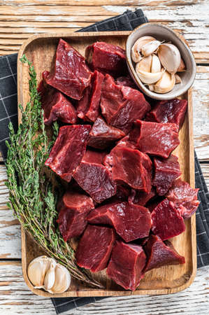 Raw sliced Beef or veal heart in a wooden tray with thyme. White wooden background. Top View Foto de archivo