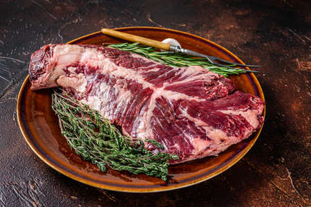 Raw hanging tender or ongle beef meat steak on rustic plate with herbs. Dark background. Top View
