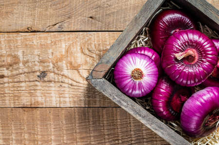 Flat red sweet onion in wooden box. Wooden background. Top View. Copy space