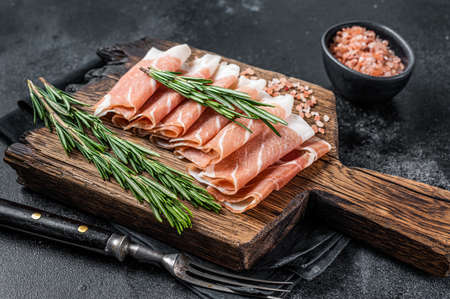 Prosciutto crudo parma ham, dry cured pork meat on a wooden board. Black background. Top View