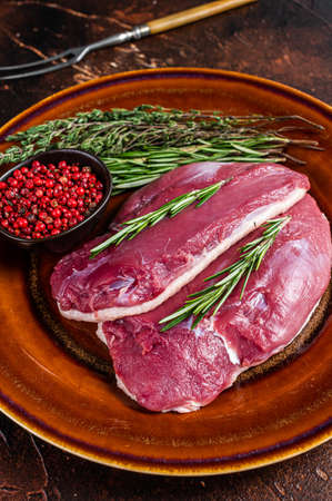 Duck raw breast steaks on rustic plate with rosemary. Dark background. Top View