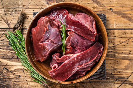 Sliced Beef or veal raw heart in a wooden plate with herbs. wooden background. Top View Foto de archivo