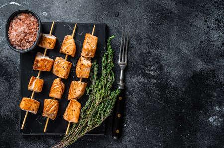 Roasted salmon kebab skewers on marble board. Black background. Top View. Copy space