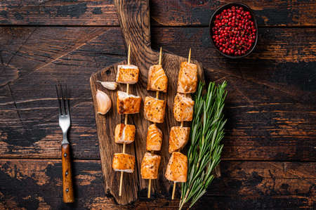 Grilled salmon fish kebab skewers on wooden board. Dark wooden background. Top View Foto de archivo