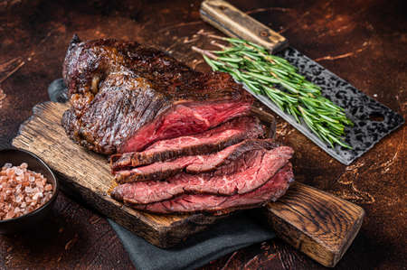Roasted hanging tender or Onglet sliced beef meat steak on a butcher board with cleaver. Dark background. Top View