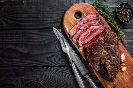 Grilled Butchers choice steak Onglet Hanging Tender beef meat on a cutting board. Black wooden background. Top View. Copy space