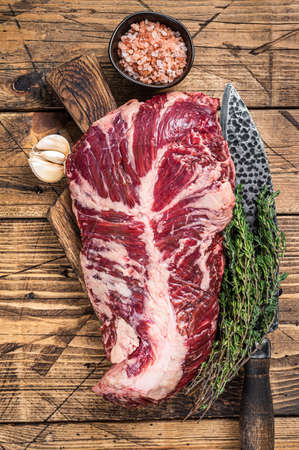 Onglet or hanger raw beef meat steak on butcher board with knife. wooden background. Top View