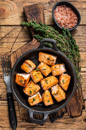 Roasted salmon or trout fish in a pan. Wooden background. Top View