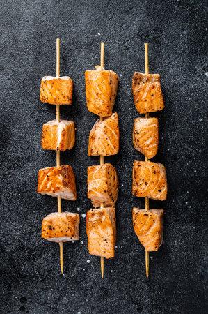 Grilled salmon kebab skewers. Black background. Top View Foto de archivo