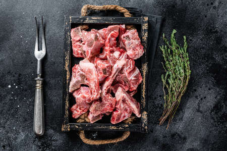 Raw diced meat with bone in a wooden tray. Black background. Top View