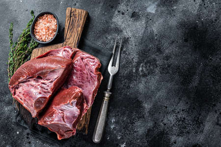 Raw cutted Beef or veal heart on a butcher board. Black background. Top View. Copy space