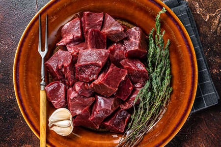 Cut Beef or veal raw heart in a rustic plate with herbs. Dark background. Top View Foto de archivo