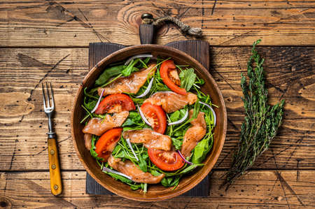 Vegetable salad with smoked salmon, arugula, tomato and green vegetables. wooden background. Top View