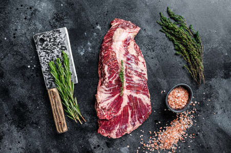 Hanger or onglet raw beef meat steak on butcher table with herbs. Black background. Top View