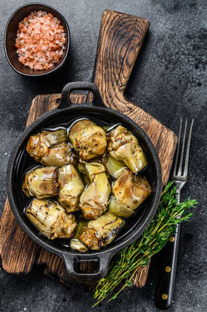 Canned artichokes in olive oil on a rustic wooden kitchen table. Black background. Top view Reklamní fotografie