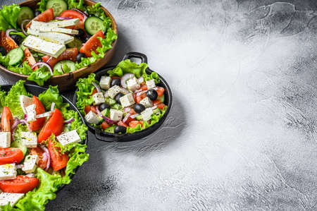 Set of ready-to-eat Greek salad in a bowl. White background. Top view. Copy space