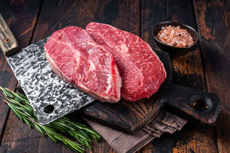 Uncooked Raw Shoulder Top Blade or flat iron beef meat steaks on a wooden butcher board with meat cleaver. Dark wooden background. Top View