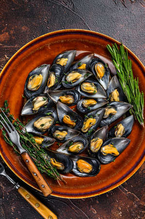 Seafood mussels with wine sauce and thyme on a plate. Dark background. Top view