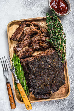Brisket BBQ beef meat sliced on a wooden tray. White background. Top view