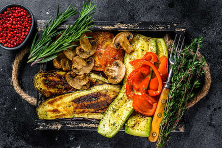 Baked vegetables bell pepper, zucchini, eggplant and tomato in a wooden tray. Black wooden background. Top view