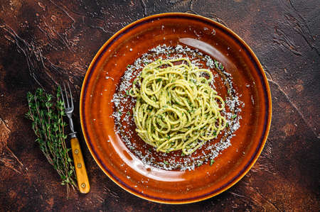Spinach Spaghetti Pasta with pesto sauce and parmesan. Dark background. Top view