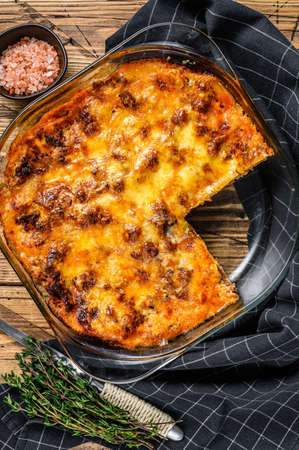 Lasagna with bolognese sauce and mince beef in a baking dish. Wooden background. Top view