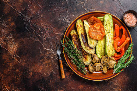 Grilled mix vegetables in a rustic plate. Dark background. Top view. Copy space