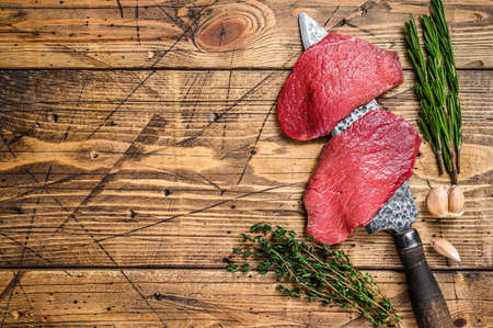 Black Angus raw beef meat sirloin steak on butcher knife. wooden background. Top view. Copy space