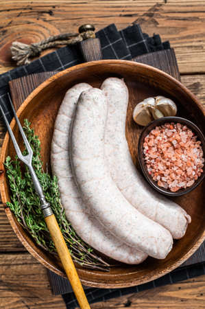 Raw Munich traditional white sausages in a wooden plate with herbs. wooden background. Top view