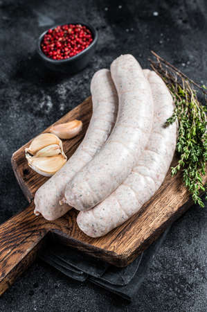 Raw Munich white sausage weisswurst on wooden board. Black background. Top view