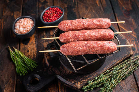 Raw kofta or lula kebabs skewers on a grill with herbs. Dark wooden background. Top view 免版税图像 - 168547922