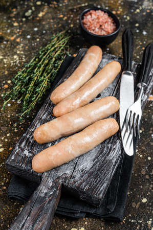 Grilled chicken sausages on a wooden board. Brown background. Top view 免版税图像