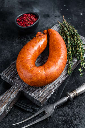 Bavarian Smoked sausage on a wooden rustic board with thyme. Black background. Top view 免版税图像