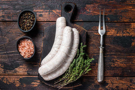 Munich traditional white sausages on a wooden board with thyme. Dark wooden background. Top view